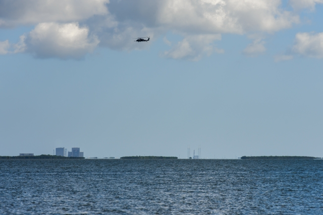 Military helicopters patrol the launch area prior to launch