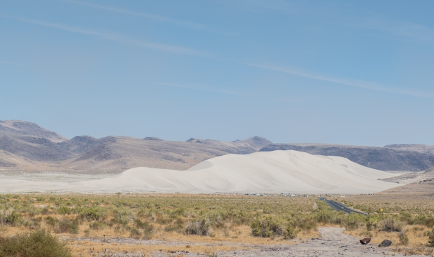 Massive mountain of sand with RVs parked near the base for scale